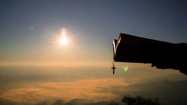 σιλουέτα άνθρωπος,το χέρι που κρατά τον Σταυρό Βίβλο,Ανατολή ηλίου